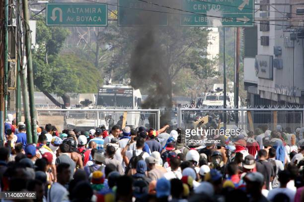Venezuelan National Guard throw tear gas to ProJuan Guaidó demonstrators as they create a barricade in the street from a house's fence after the May...