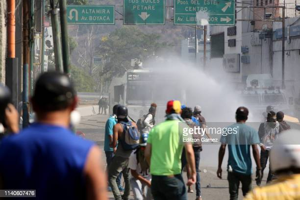 Venezuelan National Guards throw tear gas to ProJuan Guaidó demonstrators as they create a barricade in the street after the May 1 demonstration at...