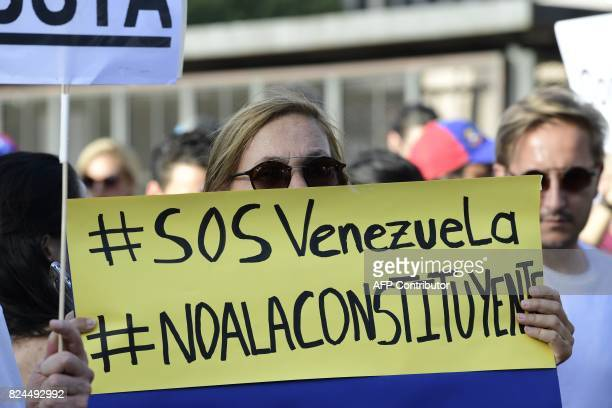 A Venezuelan national holds up a placard during a protest on July 30 2017 against Venezuelan President Nicolas Maduro and the election of a...