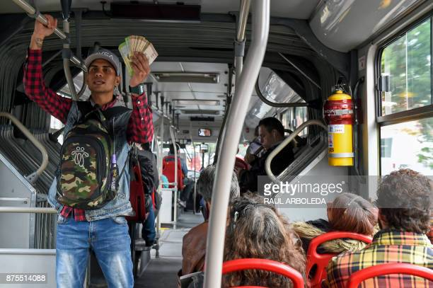 Venezuelan national Jhonger Pina sells candies and shows Bolivar bills as a curiosity to passengers in exchange for local coins on a bus in Bogota on...