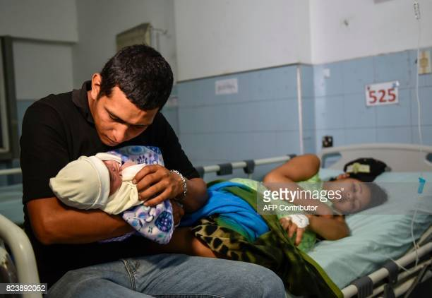 Venezuelan national Jose Luis Gonzales holds his newborn as his wife Brecia Triago rests at the Erasmo Meoz University Hospital in Cucuta North of...