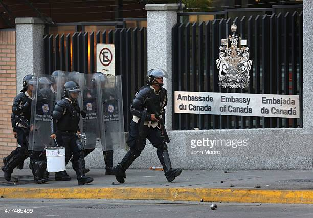 Venezuelan national policemen pas the Canadian Embassy while advancing on antigovernment demonstrators on March 6 2014 in Caracas Venezuela...