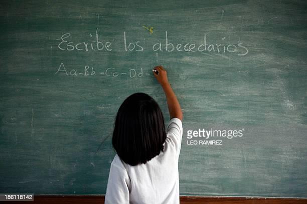 A Venezuelan native girl writes on the chalkboard at the Esperanza multiethnical school in Puerto Ayacucho in the Venezuelan state of Amazonas on...