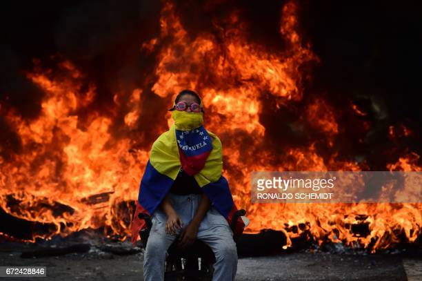 Venezuelan opposition activist is backdropped by a burning barricade during a demonstration against President Nicolas Maduro in Caracas, on April 24,...
