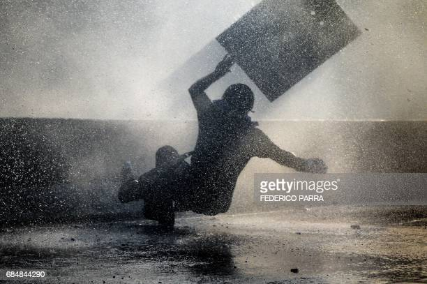 Venezuelan opposition activist slips while clashing with the riot police during a rally against the government of President Nicolas Maduro in Caracas...