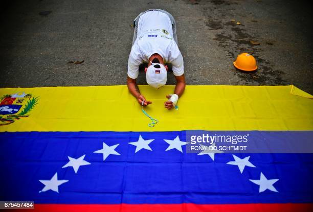 TOPSHOT Venezuelan opposition activists attend a march against President Nicolas Maduro in Caracas on May 1 2017 May Day protests risk being rough in...