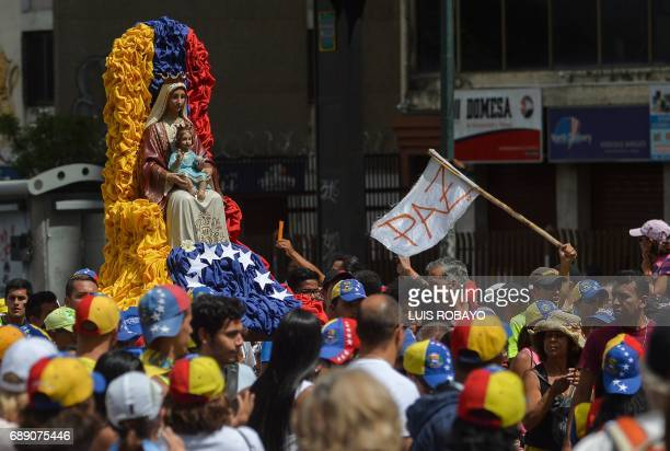 Venezuelan opposition activists carry an image of the Virgin of Coromoto during a march for peace in Caracas on May 27 2017 Demonstrations that got...
