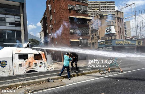 TOPSHOT Venezuelan opposition activists clash with the police during a protest against the government of President Nicolas Maduro on April 6 2017 in...