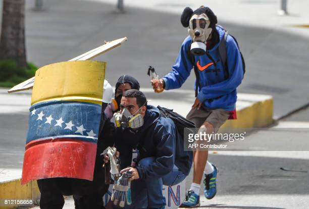 TOPSHOT Venezuelan opposition activists remain behind a shield as they clash with riot police during a protest against Venezuelan President Nicolas...