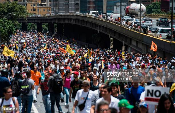 TOPSHOT Venezuelan opposition activists take part in a protest blocked by the National Guard against the government of President Nicolas Maduro at...
