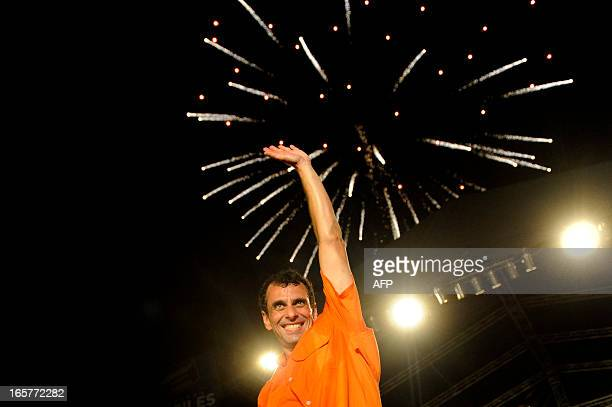 Venezuelan opposition candidate Henrique Capriles waves during a campaign rally in Puerto Ordaz Bolivar state Venezuela on April 5 2013 One month...