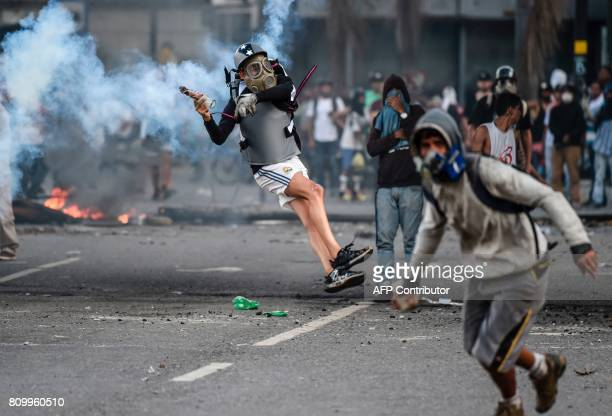 TOPSHOT Venezuelan opposition demonstrators blocking the avenue during a protest against President Nicolas Maduro clash with riot police in Caracas...