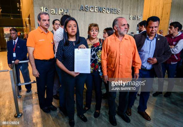 Venezuelan opposition deputy Gaby Arellano shows the document submitted to the Obudsman Office demanding the beginning of a process to dismiss...