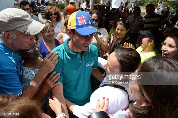 Venezuelan opposition figure and outgoing governor of Miranda Henrique Capriles is greeted by supporters at a polling station in Caracas'...
