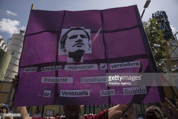 Venezuelan opposition holds a poster inviting Military Forces to recognize Juan Guaido as president during a protest against Maduros government in...