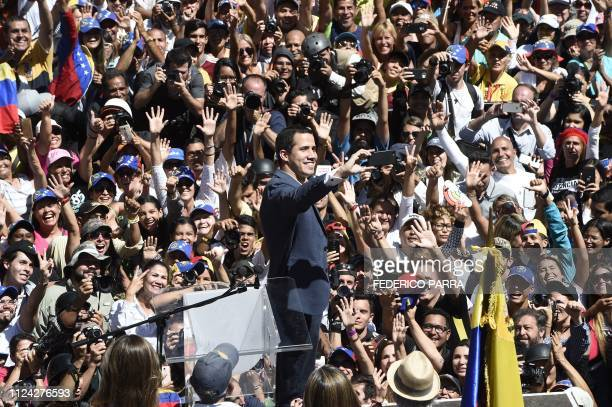 Venezuelan opposition leader and self declared acting president Juan Guaido takes a selfie with supporters during a rally to press the military to...