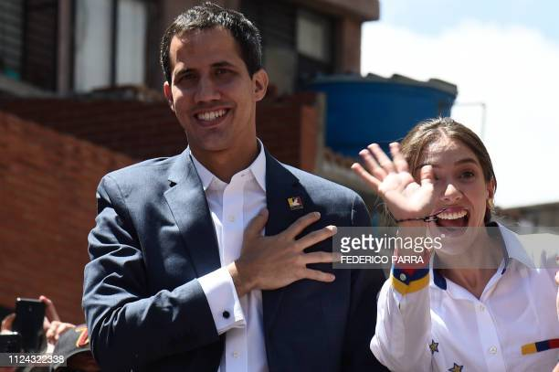 TOPSHOT Venezuelan opposition leader and self declared acting president Juan Guaido accompanied by his wife Fabiana Rosales gestures at supporters...