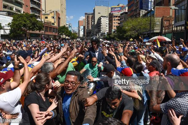 TOPSHOT Venezuelan opposition leader and self declared acting president Juan Guaido leaves after a rally in eastern Caracas on February 12 2019...