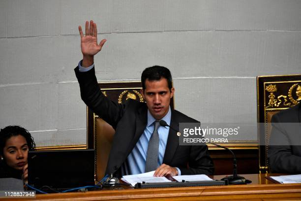 Venezuelan opposition leader and self-proclaimed acting president Juan Guaido raises his hand during a session of the Venezuelan National Assembly in...