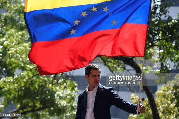 Venezuelan opposition leader and self-proclaimed acting president Juan Guaido is pictured under a national flag during a gathering with supporters...
