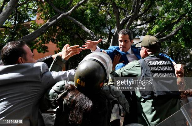 Venezuelan opposition leader and self-proclaimed acting president Juan Guaido is blocked by security forces as he tries to reach the National...