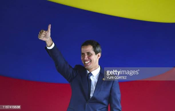 Venezuelan opposition leader and self-proclaimed interim president Juan Guaido gives the thumb up after voting for rejoining the Inter-American...