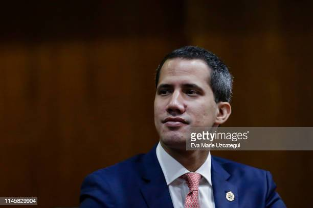 Venezuelan opposition leader Juan Guaido recognized by many members of the international community as the country's rightful interim ruler looks on...