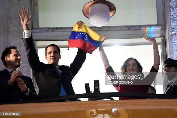 Venezuelan opposition leader Juan Guaido waves a Venezuelan flag next to Madrid's regional president Isabel Diaz Ayuso during his visit to Madrid on...