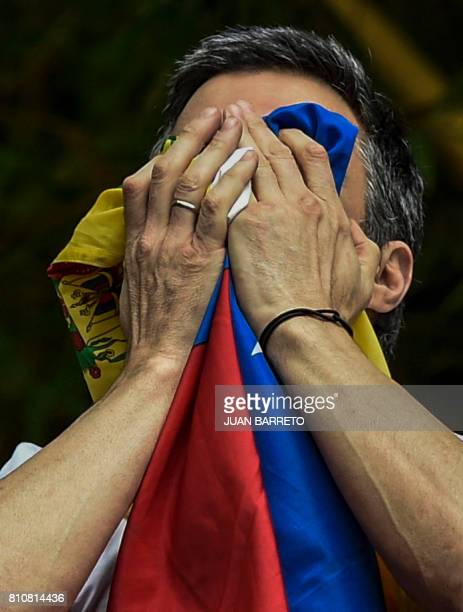 Venezuelan opposition leader Leopoldo Lopez kisses the Venezuelan national flag as he greets supporters gathering outside his house in Caracas after...