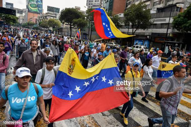 Venezuelan opposition supporters take part in a a march on the anniversary of 1958 uprising that overthrew military dictatorship in Caracas on...