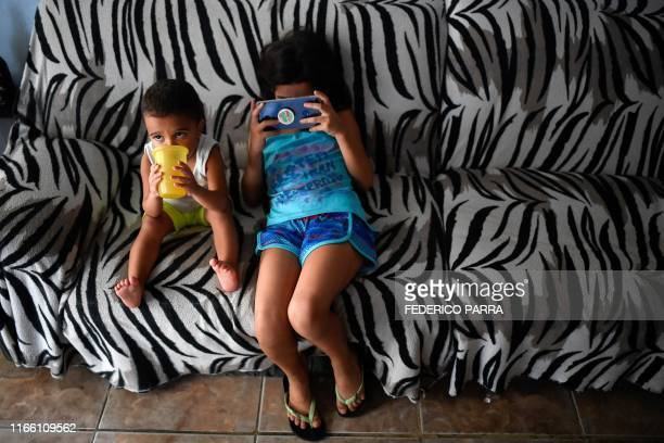 TOPSHOT Venezuelan Paola Osorio and her brother whose parents emigrated remain at their house of the San Agustin neighborhood in Caracas on August 5...