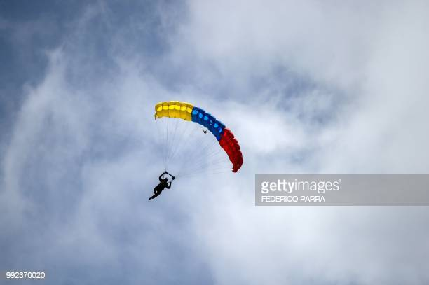 Venezuelan paratroopers jump out of an airplane during a military parade to celebrate the 207th anniversary of the Venezuelan Independence in Caracas...