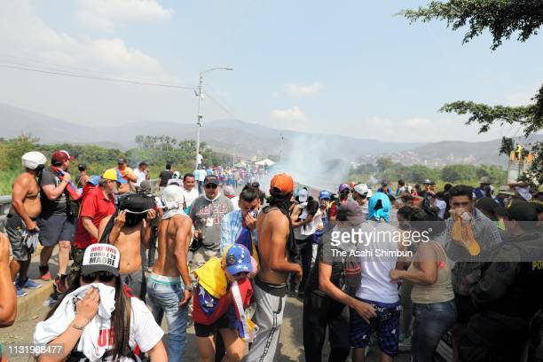 Venezuelan people escape from tear gas shot by Venezuelan National Guard soldiers who close at the Simon Bolivar international bridge on February 23...