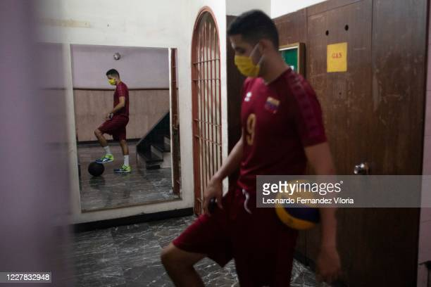 Venezuelan player of the national volleyball squad Jose Chema Carrasco wearing a face mask waits the elevator as training in isolation during the...