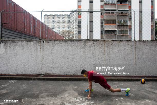 Venezuelan player of the national volleyball squad Jose Chema Carrasco stretches before training in isolation during the radical quarantine to stop...