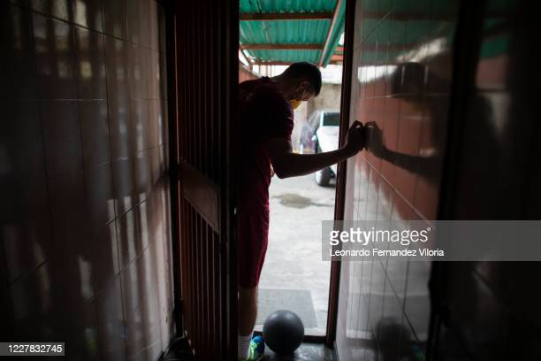 Venezuelan player of the national volleyball squad Jose Chema Carrasco opens the parking lot door as training in isolation during the radical...