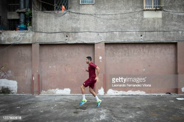 Venezuelan player of the national volleyball squad Jose Chema Carrasco runs in a space with less than 40 square meters as training in isolation...