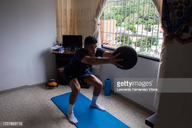 Venezuelan player of the national volleyball squad Jose Chema Carrasco squats position whit a medicine ball as training in isolation in his 70 square...