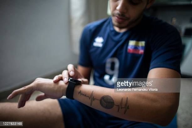 Venezuelan player of the national volleyball squad Jose Chema Carrasco adjusts the time on his watch before training in isolation in his 70 square...