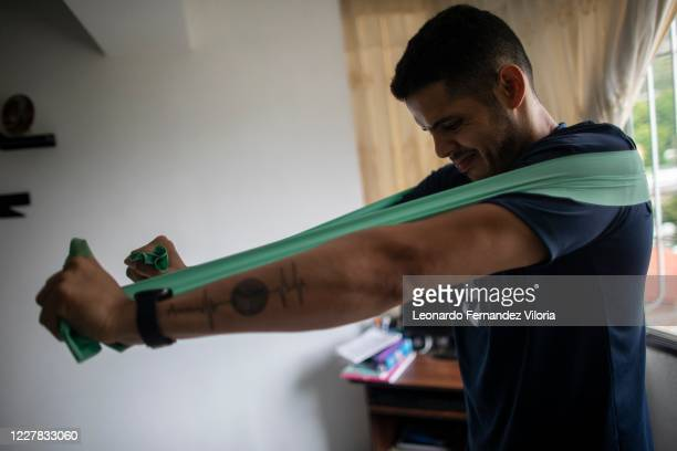 Venezuelan player of the national volleyball squad Jose Chema Carrasco uses an elastic band as training in isolation at his 70 square meter apartment...