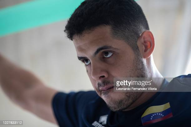 Venezuelan player of the national volleyball squad Jose Chema Carrasco uses an elastic band as training in isolation in his 70 square meter apartment...