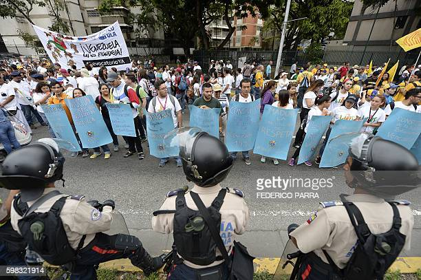 TOPSHOT Venezuelan police in riot gear face demonstrators before an opposition march in Caracas on September 1 2016 Venezuela's opposition and...