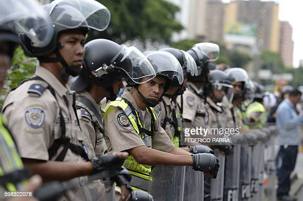 Venezuelan police in riot gear face demonstrators before an opposition march in Caracas on September 1 2016 Venezuela's opposition and government...