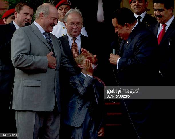 Venezuelan President Hugo Chavez give five to Nikolai Lukashenko the son of his Belarussian counterpart Alexander Lukashenko , during a meeting at...