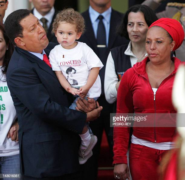 Venezuelan president Hugo Chavez holds in his arms Colombian politician Consuelo Gonzalez´s granddaughter next to Colombian politician Clara Rojas...