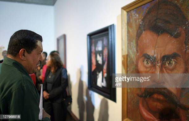 Venezuelan President Hugo Chavez looks at a portrait of Mexican revolutionary leader Emiliano Zapata at the Fine Arts Museum in Caracas on April 10...
