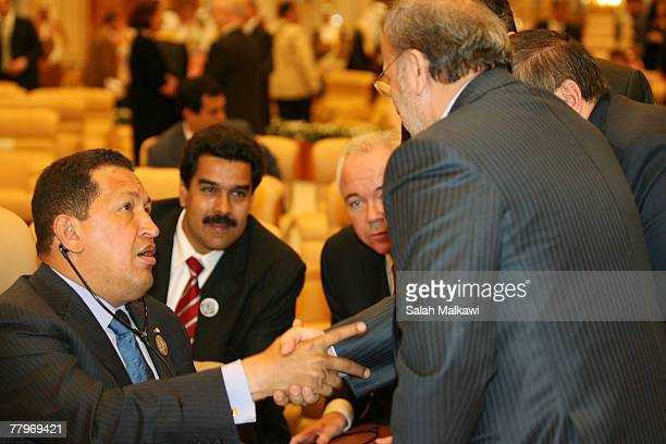 Venezuelan President Hugo Chavez shakes hands with Iran's Foreign Minister Manouchehr Mottaki at the closing of the Third OPEC Summit November 18...