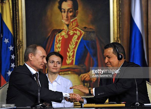 Venezuelan President Hugo Chavez shakes hands with Russian Prime Minister Vladimir Putin during his visit to Miraflores presidential palace in...