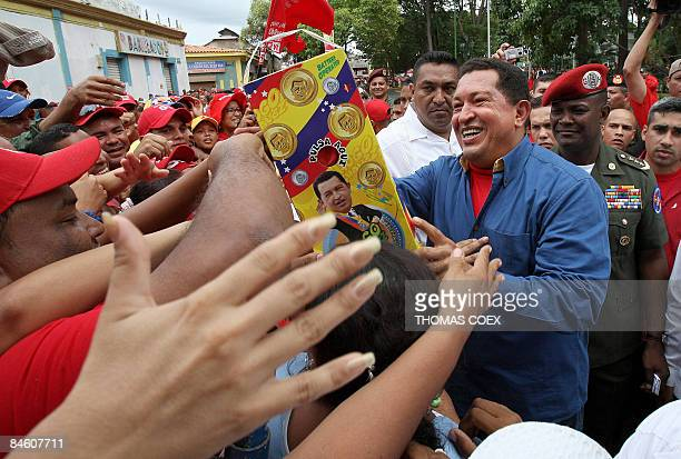 Venezuelan President Hugo Chavez shakes the hands of supporters during a visit to the city of Cumana state of Sucre 275 kms east of Caracas on...
