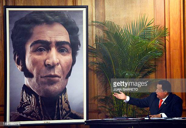 Venezuelan President Hugo Chavez shows a picture showing the possible face of Liberator Simon Bolivar a digital rendering from genetic data following...